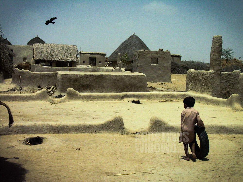 pakistan-2005-thar-desert-deserted-village-boy-bird-hut-hot
